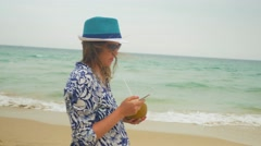 Pregnant woman walking along the sea with coconut and typing a massage with a - stock footage