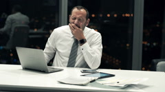 Tired businessman with laptop yawning in the office during night - stock footage