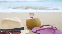 Coconut with drinking straw, hat, sunglasses and beach slippers on a sand at the - stock footage