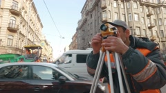 RUSSIA ST.PETERBURG- engineer looks at Total Station in the city Stock Footage