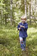 Boy walking through forest carrying stick Stock Photos
