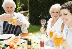 Group of people enjoying food and drink outdoors Stock Photos