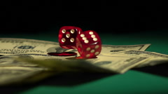 Red dice falling on money, gambler playing game at casino, addiction to gambling Stock Footage