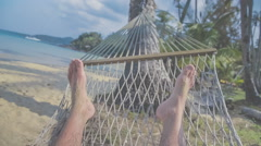 Feet swinging in a hammock, POV. Relaxing on the beach with sea view Stock Footage