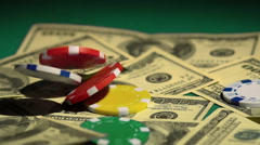 Gambling in casino, lots of colored chips falling upon money on green table Stock Footage