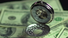 Closeup of vintage pocket watch hanging above money, precious time passing by Stock Footage
