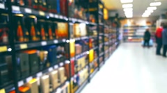 Shoppers in a supermarket, liquor department, blurred background Stock Footage