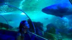 Caucasian woman walking in aquarium tunnel and looking up through the glass at a Stock Footage