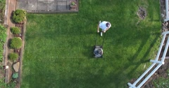 Aerial View Man Cutting Grass with Push Lawnmower - stock footage