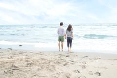 Young couple holding hands beach - stock photo