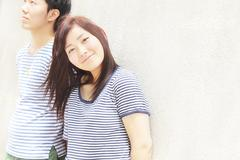 Portrait of young couple wearing striped top garments - stock photo