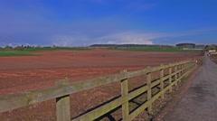 British Farming Agriculture - tractors ploughing and sewing seed in a field Stock Footage