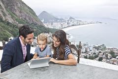 Young family using laptop, Casa Alto Vidigal, Rio De Janeiro, Brazil Stock Photos