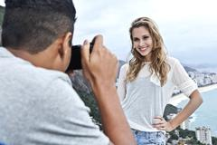 Young man photographing girlfriend, Casa Alto Vidigal, Rio De Janeiro, Brazil - stock photo