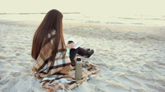 Beautiful woman drink tea reading book on the beach Stock Footage