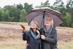 Senior couple under umbrella checking for rain - stock photo