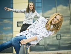 Two young women balanced on railings Stock Photos