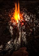 Blacksmith holding metal knife in furnace Stock Photos