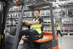 Forklift truck driver in engineering warehouse Kuvituskuvat