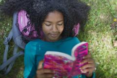 Close up of girl reading in park Stock Photos