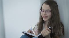 Emotional little girl with glasses writes in diary and laughing Stock Footage