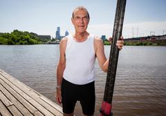 Senior man on pier holding oars - stock photo