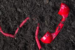 Red retro telephone handset buried in soil Stock Photos