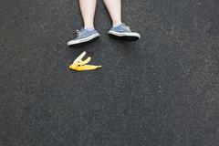 Pair of legs and banana skin on tarmac Stock Photos