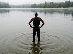 Young man in wet suit preparing to swim lake Stock Photos