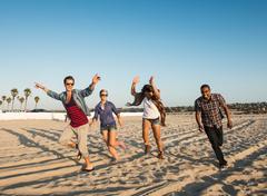 Friends running on Mission Beach, San Diego, California, USA - stock photo