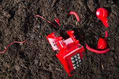 Red retro telephone buried in soil - stock photo