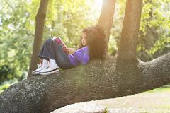 Young girl lying on tree branch reading book Stock Photos