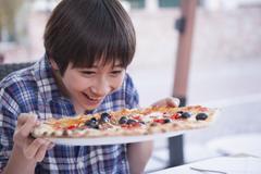 Boy holding pizza Stock Photos