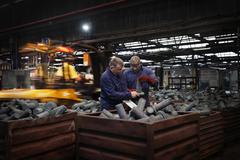 Checking dimensions on crank shafts in warehouse area as fork lift truck unloads Stock Photos