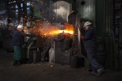 Sparks fly as counterblow hammer forms flight bar, the counterblow hammer forges Stock Photos