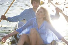 Young romantic couple splashing around in rowing boat Kuvituskuvat