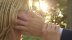 Groom softly touches bride's face close up. Beautiful sunset on background Stock Footage