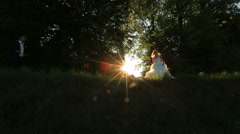 Lovely blonde bride and groom dancing outdoor in the sunset light, looking happy Stock Footage