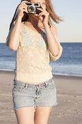 Young woman holding camera on beach, Breezy Point, Queens, New York, USA Stock Photos