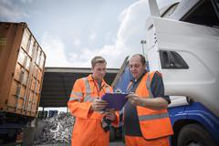 Worker inspecting delivery paperwork with truck driver - stock photo