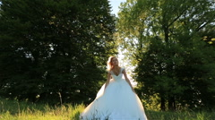 Attractive young blonde bride jumping and having fun in the green meadow in Stock Footage