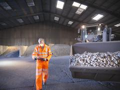 Worker checking clipboard in mineral store passing digger full of metal alloy Stock Photos