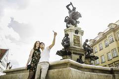 Young couple taking self portrait photograph beside statue in Augsburg, Bavaria, Stock Photos