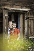 Couple looking out from chalet window, Achenkirch,  Tyrol, Austria - stock photo