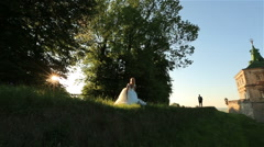 Happy young blonde bride in white dress and groom in suit having fun and jumping Stock Footage