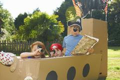 Two brothers and sister playing with homemade pirate ship in garden Stock Photos
