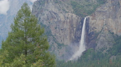 Yosemite Falls thunders down the canyon side of the valley Stock Footage