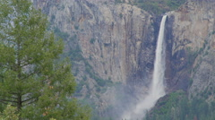 Mist from Yosemite falls blows along canyon Stock Footage
