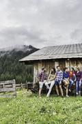 Group of friends chatting behind wooden shack, Tirol, Austria - stock photo