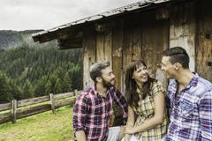 Friends chatting behind wooden shack, Tirol, Austria Stock Photos
